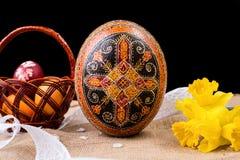 Pysanka, huevos pintados en busket y narcisos de la primavera Huevos de Pascua en fondo negro Concepto del día de fiesta Pascua é Fotografía de archivo