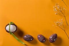 Pysankies de madera y huevo blanco en cesta en fondo anaranjado imagen de archivo libre de regalías