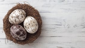 Easter eggs in the nest on wooden background stock photos