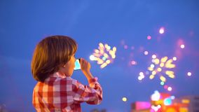 Pysbarn som filmar bilder av härliga fyrverkerier i skärm för natthimmel av mobiltelefonen Händer av behandla som ett barn att ta lager videofilmer