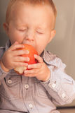 Pysbarnunge som hemma äter äpplefrukt royaltyfria bilder