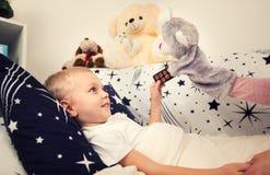 Pysen är sjuk, ligger på sängen barnförkylningar som dricker sjukt sött sirapbarn för flicka royaltyfri fotografi