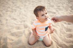 Pysen äter icecream från moderhanden; Fotografering för Bildbyråer