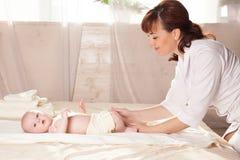 Pysen behandla som ett barn doktorn som gör massage Arkivfoto