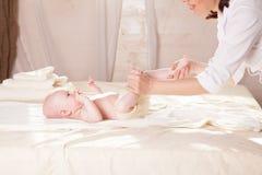 Pysen behandla som ett barn doktorn som gör massagehänder och ben och, drar tillbaka Arkivbilder