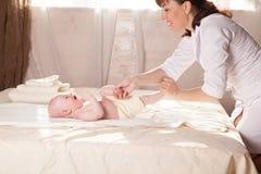 Pysen behandla som ett barn modern som gör massagehänder och ben Fotografering för Bildbyråer