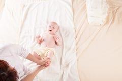 Pysen behandla som ett barn modern som gör massagehänder och ben Royaltyfri Foto