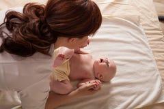 Pysen behandla som ett barn modern som gör massagehänder och ben Arkivfoto