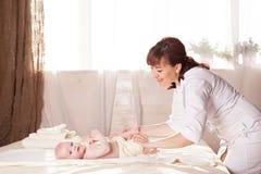 Pysen behandla som ett barn modern som gör massagehänder och ben Arkivbild