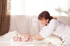 Pysen behandla som ett barn modern som gör massagehänder och ben Royaltyfria Bilder