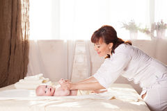 Pysen behandla som ett barn modern som gör massagehänder och ben Royaltyfri Bild