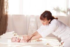 Pysen behandla som ett barn modern som gör massagehänder och ben Royaltyfri Fotografi