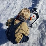 Pysen blont hår som spelar i vinter med snö, bygger snögubben Bärande jeans och halsduk Royaltyfri Fotografi