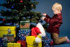 Pysen dekorerar julgranen Gran med garneringar Unge och prydnad Arkivbild