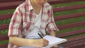 Pysen drar i hans anteckningsbok på bänken fotografering för bildbyråer