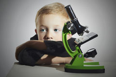 Pysen gör inte ska inte studera SAD barn Skolpojke som arbetar med ett mikroskop smart pojke Utbildning Arkivbild