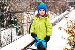 Pysen gör kastar snöboll med kastar snöboll tillverkaren lycklig leka snow för barn Kallt vinterväder Vinteraktiviteter för ungar arkivbilder