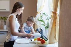 Pysen hjälper mamman i köket royaltyfri fotografi