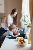 Pysen hjälper mamman i köket Arkivbild