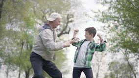 Pysen i en rutig skjorta och den positiva gamala mannen som visar sig muskler i, parkerar Farfar och lager videofilmer