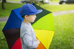 Pysen i hatt med det flerfärgade paraplyet parkerar in efter regn på solig sommardag Arkivfoto