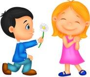 Pysen knäfaller på ett knä som ger blommor till flickan Fotografering för Bildbyråer