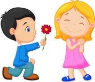 Pysen knäfaller på ett knä som ger blommor till flickan Arkivfoton