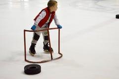 Pysen lär att åka skridskor med hjälpen av speciala stöttande portar på ishockeyarenan, April 14, 2018, Vitryssland arkivfoto