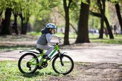 Pysen lär att rida en cykel i parkerar Den gulliga pojken i solglasögon rider en cykel Lyckligt le barn i hjälm som rider cykla royaltyfri fotografi