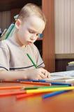 Pysen lärer att teckna med blyertspennor Arkivbild