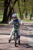 Pysen l?r att rida en cykel i parkerar Den gulliga pojken i solglas?gon rider en cykel Lyckligt le barn i hj?lm som rider cykla royaltyfri bild