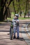 Pysen l?r att rida en cykel i parkerar Den gulliga pojken i solglas?gon rider en cykel Lyckligt le barn i hj?lm som rider cykla royaltyfria bilder