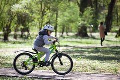 Pysen l?r att rida en cykel i parkerar Den gulliga pojken i solglas?gon rider en cykel Lyckligt le barn i hj?lm som rider cykla royaltyfri foto