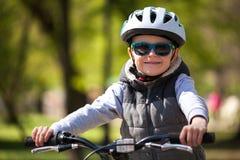 Pysen l?r att rida en cykel i parkerar Den gulliga pojken i solglas?gon rider en cykel Lyckligt le barn i hj?lm som rider cykla arkivfoton
