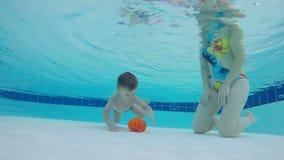 Pysen lyfter en leksak från undervattens- med hans moders hjälp stock video