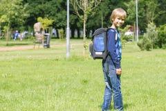 Pysen med en ryggsäck går till skolan tillbaka sikt Arkivbild