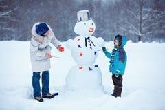 Pysen med hans fostrar att måla en snowman Royaltyfri Foto