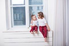Pysen och flickan bara hemma som håller ögonen på i fönstret arkivfoto