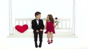 Pysen och flickan sitter lite på en gunga, gullig pratstund Vit bakgrund långsam rörelse stock video