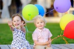 Pysen och flickan som har gyckel och, firar födelsedagpartiet med färgrika ballonger Royaltyfri Bild