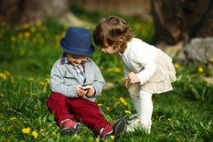 Pysen och flickan som leker med mobil, ringer Arkivbild