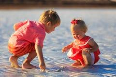 Pysen och flickan spelar, drar på sandstranden Arkivbilder