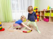 Pysen och flickan spelar med leksakjärnvägen i dagis royaltyfria bilder