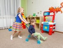 Pysen och flickan spelar med leksaksittvagnen hemma arkivfoto
