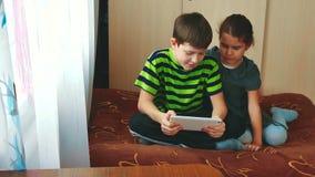 Pysen och flickan spelar på minnestavlan som ligger på sängen internet för massmedia för pojke- och flickatonår social på en minn arkivfilmer