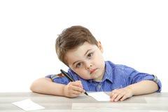 Pysen sitter och drar skriver på en isolerad bakgrund royaltyfri foto