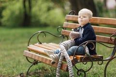 Pysen sitter på bänken med hans leksak Arkivbild