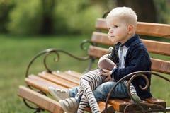 Pysen sitter på bänken med hans leksak Royaltyfria Foton