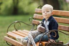 Pysen sitter på bänken med hans leksak Arkivbilder