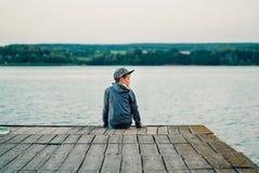 Pysen sitter på bron nära sjön arkivbild